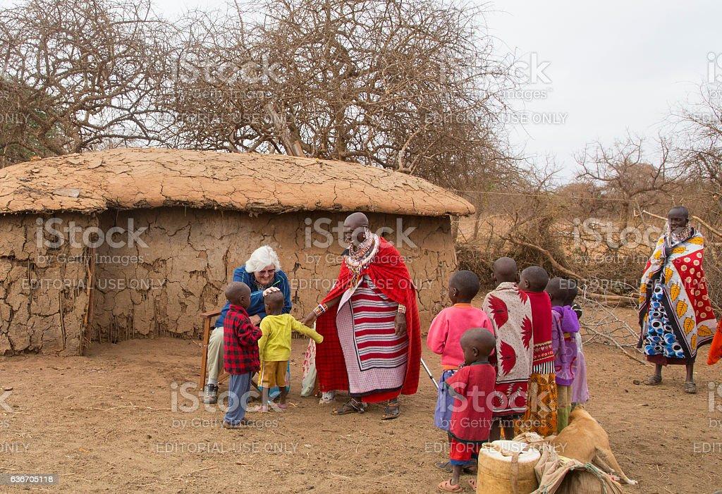 Senior tourists in Maasai village. Greeting children. stock photo