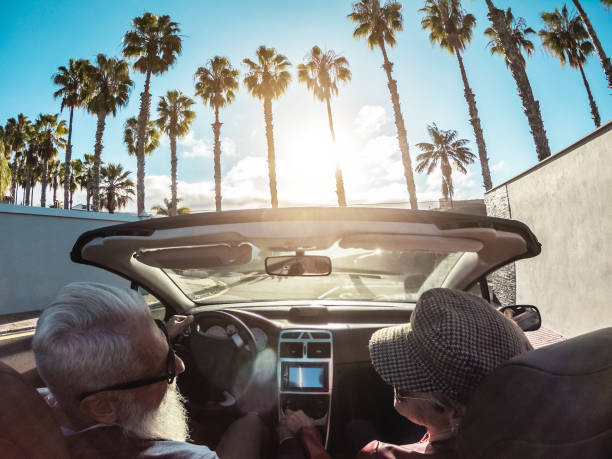 Senior trendy couple inside a convertible car - Mature people having fun doing a road trip in a tropical place - Travel, fashio and joyful elderly concept - Main focus on woman hat stock photo