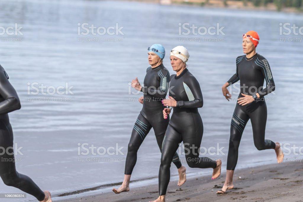 Three older triathletes run along the sandy beach in their wetsuits,...