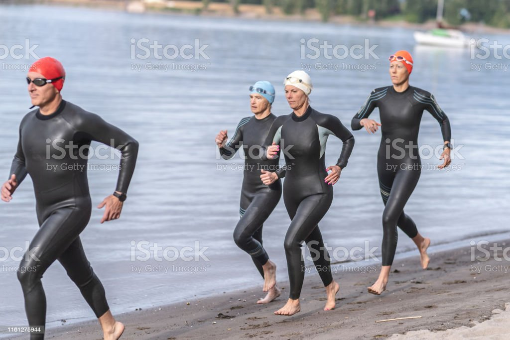 Senior triathletes run along the sandy beach in their wetsuits,...