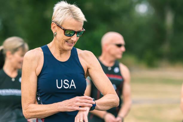 senior triathleten helfen einander vor dem rennen - laufende tattoos stock-fotos und bilder