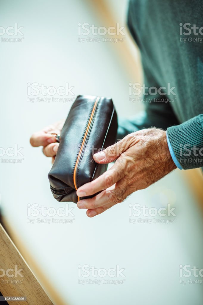 Close-up of hands of an unrecognizable senior male person zipping a...