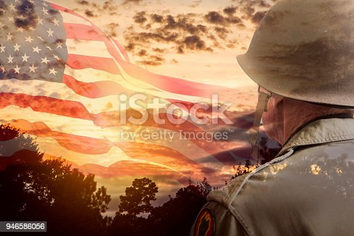 Senior adult man, USA army soldier overlay on dramatic sunset sky and waving American flag.   Pensive look toward the sky.