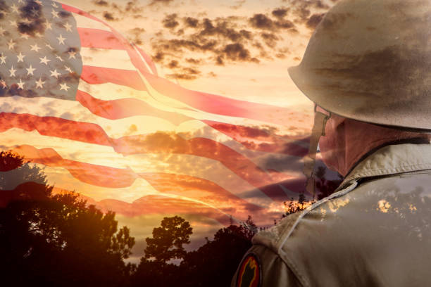 Senior USA army soldier overlay sunset, American flag. Senior adult man, USA army soldier overlay on dramatic sunset sky and waving American flag.   Pensive look toward the sky. independence day photos stock pictures, royalty-free photos & images