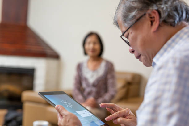 Senior Using a Home Control App on a Computer Tablet stock photo