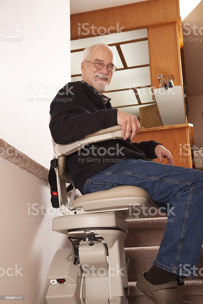 Senior using stairlift in home: Assisted Living stock photo