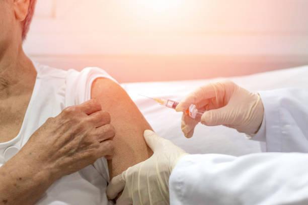 senioren-impfkonzept. ältere bekommen immunimpfstoff am arm für grippe, lungenentzündung, und gürtelrose (mmr) im krankenhaus von krankenschwester. arzt gibt eine injektion an ältere menschen patienten in der klinik. - gürtelrose stock-fotos und bilder