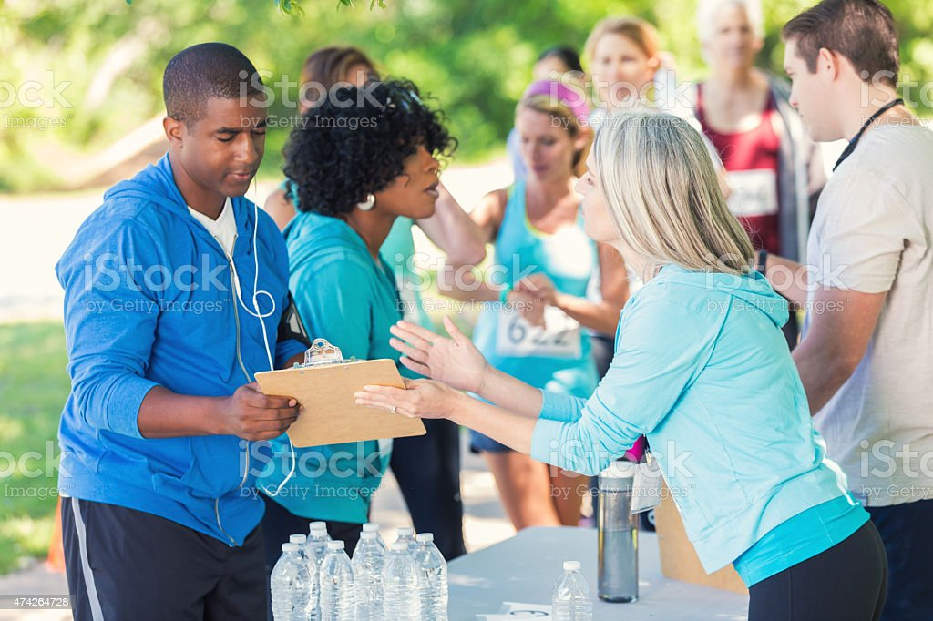Senior volunteer helping African American man register for marathon stock photo