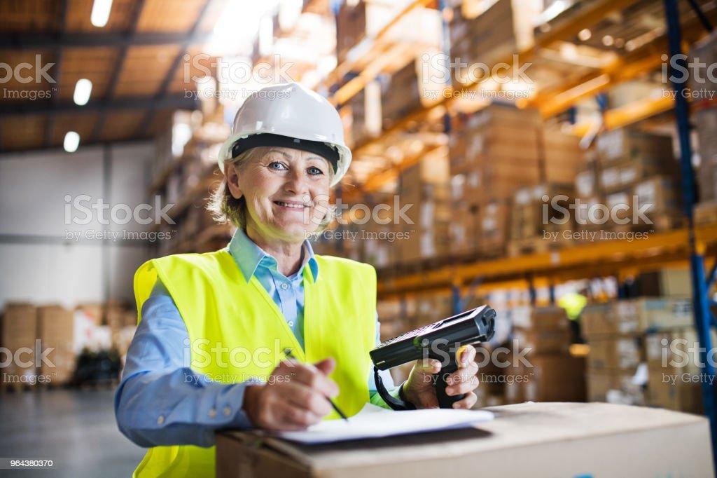 Senior vrouw magazijnmedewerker met barcodescanner. - Royalty-free Actieve ouderen Stockfoto