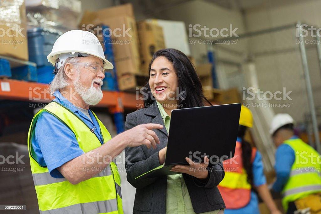 Senior trabajador de almacén mujer hispana mediante computadora portátil con el supervisor foto de stock libre de derechos