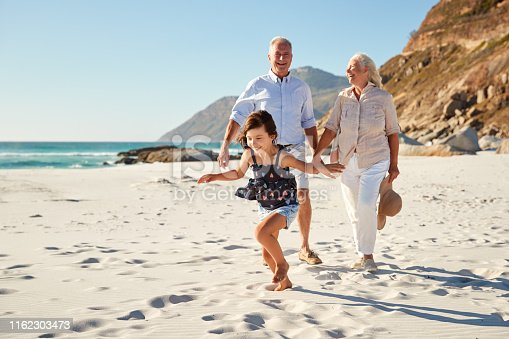 Senior white couple and their granddaughter walking on a sunny beach, close up