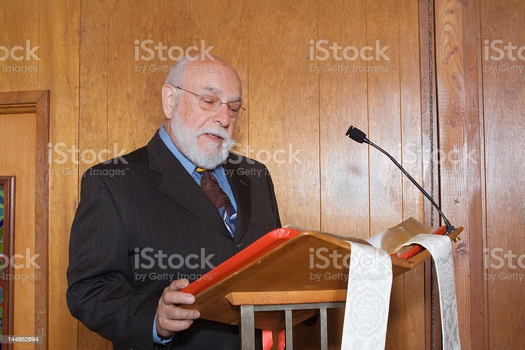 Senior White Man in Church Reading from Bible at Lectern stock photo