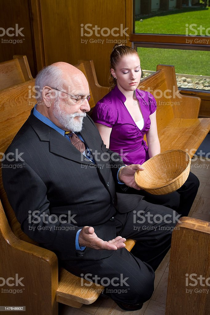 Senior White Man Young Woman Looking at Empty Offering Basket royalty-free stock photo