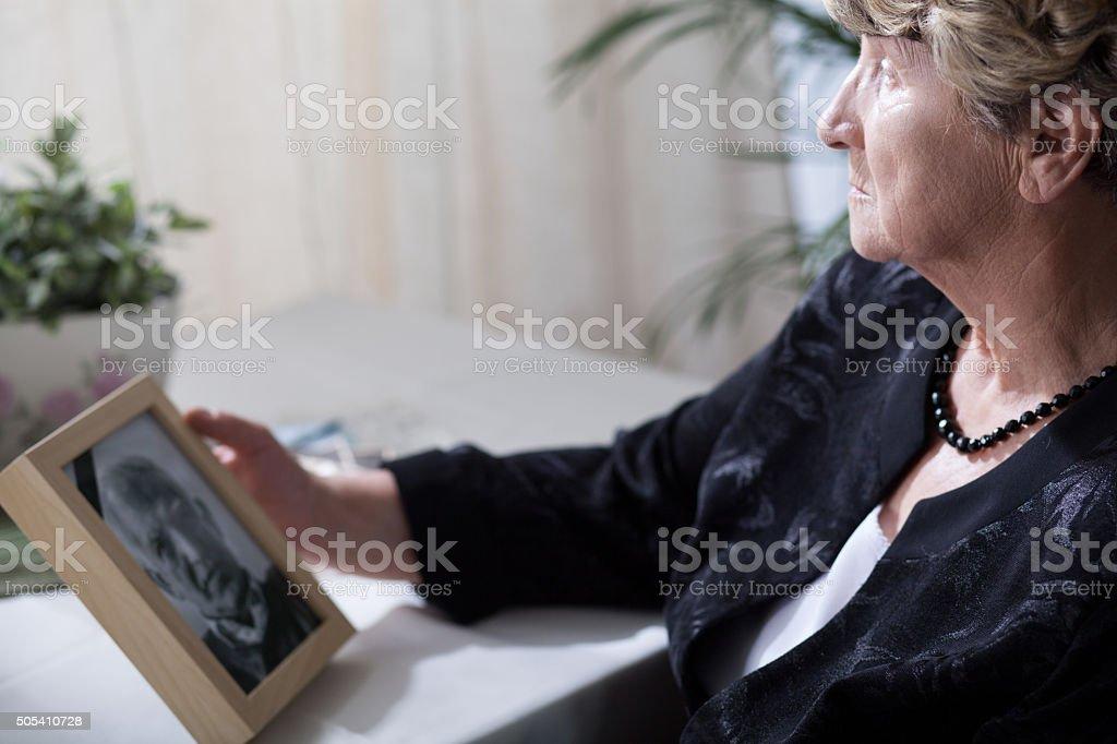 Senior widow reminiscing her husband stock photo