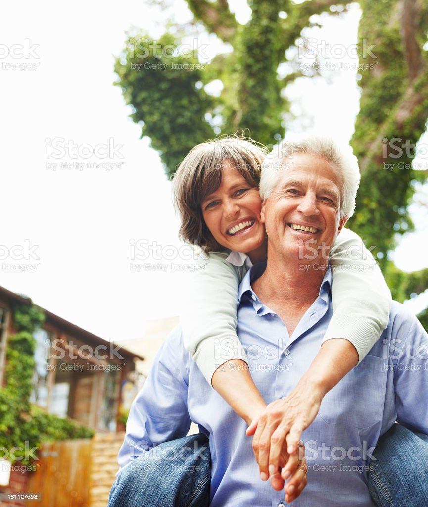 Senior wife piggybacking on her husband royalty-free stock photo