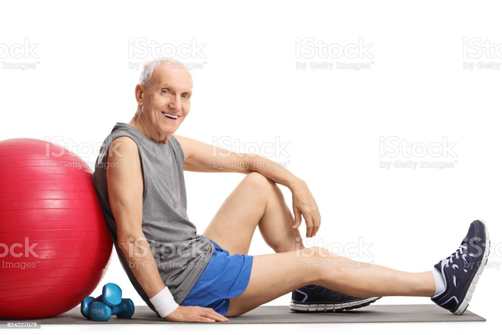 Senior with a pilates ball and dumbbells stock photo