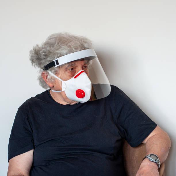 senior with aniviral mask and helmet - ffp2 imagens e fotografias de stock