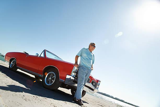 senior mit klassischen cabrio auto - alten muscle cars stock-fotos und bilder