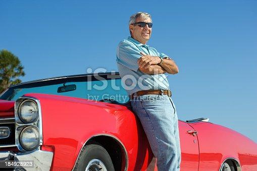istock Senior with classic convertible car 184928923