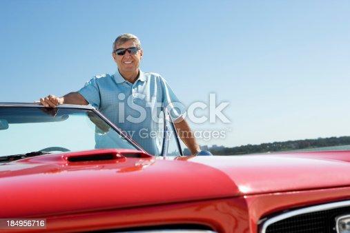 istock Senior with classic convertible car 184956716