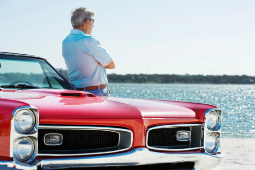 Senior adult on the beach with a restored 1967 convertible.
