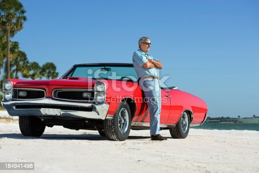 530979971istockphoto Senior with classic GTO convertible car 184941498