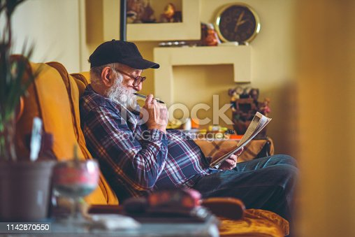 The senior with crossword  spends his free time