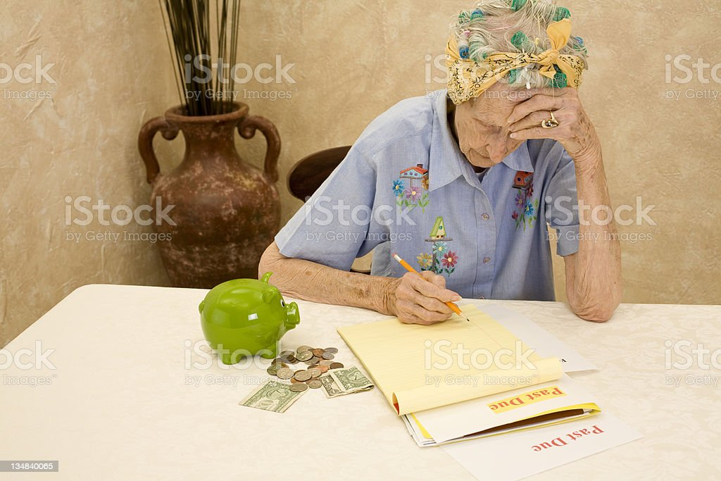 Senior with financial concerns and piggybank royalty-free stock photo