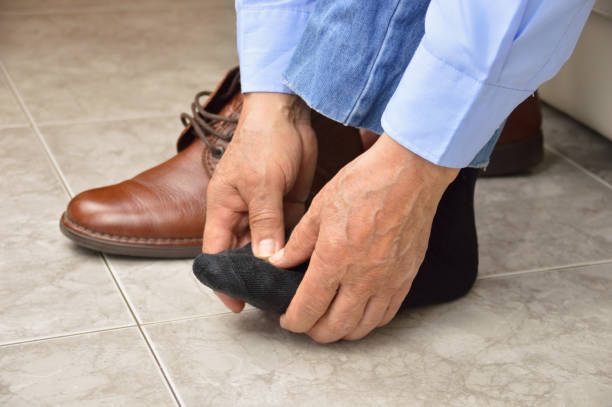 senior with foot pain Cropped shot of an unrecognizable man suffering with foot cramp in the room foot stock pictures, royalty-free photos & images