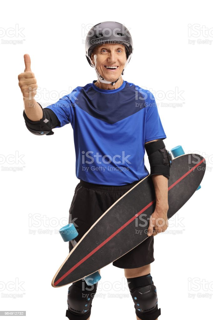Senior with protective gear and longboard making a thumb up sign royalty-free stock photo