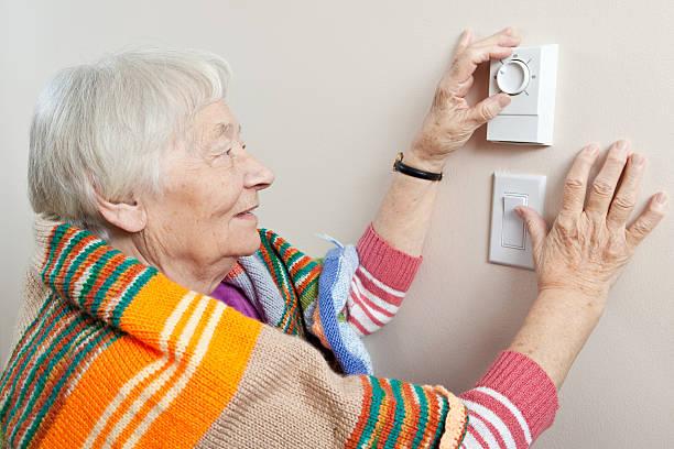senior frau anpassen ihre thermostat - seniorenwohnungen stock-fotos und bilder