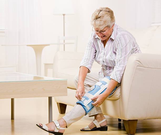 Senior Woman Adjusting Knee Brace stock photo