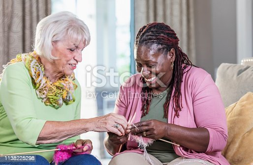 A senior woman in her 70s and her friend, a mature African-American woman in her 50s, sitting indoors, conversing and knitting. They are relaxed and smiling.