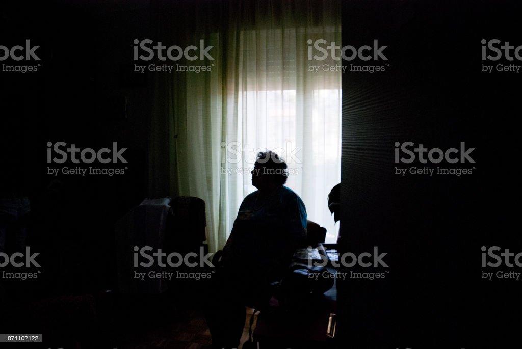 Senior Woman Alone in Dark Room stock photo