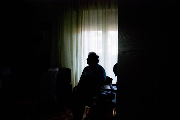 Senior Woman Alone in Dark Room Senior Woman Alone in Dark Room. desolation stock pictures, royalty-free photos & images
