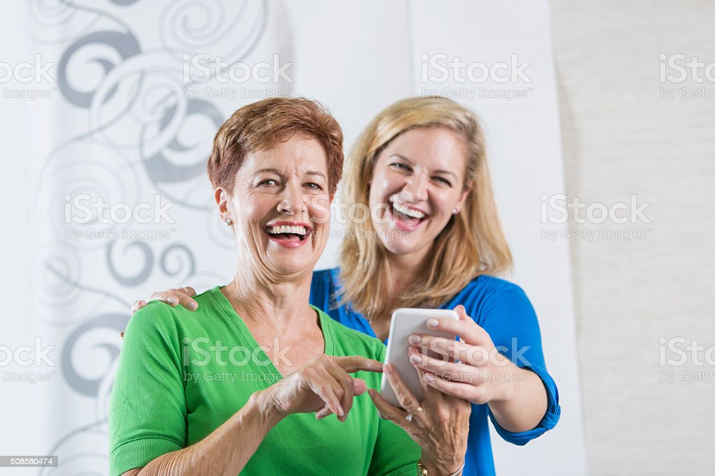A senior woman holding a mobile phone up to share something funny...