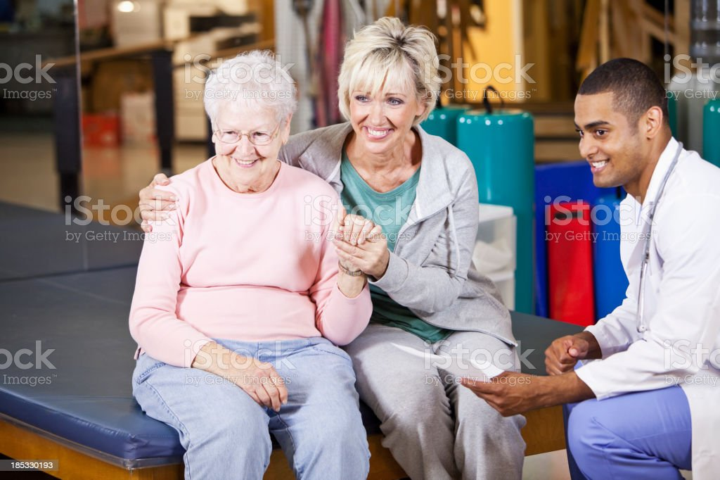 Senior woman and adult daughter with physical therapist stock photo