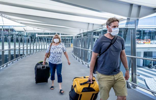 Senior In und erwachsenen Sohn tragen Gesichtsmaske am Flughafen aus Angst vor Coronavirus und Reiseverbot und internationalen Reisen Stornierungen zur Seuchenbekämpfung und Prävention von COVID-19 Ausbruch Pandemie. – Foto