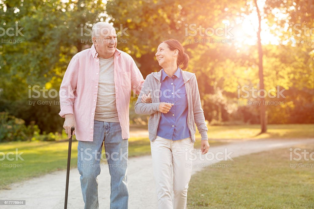 senior woman and caregiver go walking outdoors stock photo