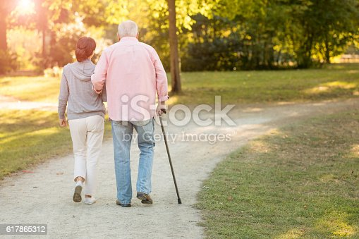istock senior woman and caregiver go walking outdoors 617865312