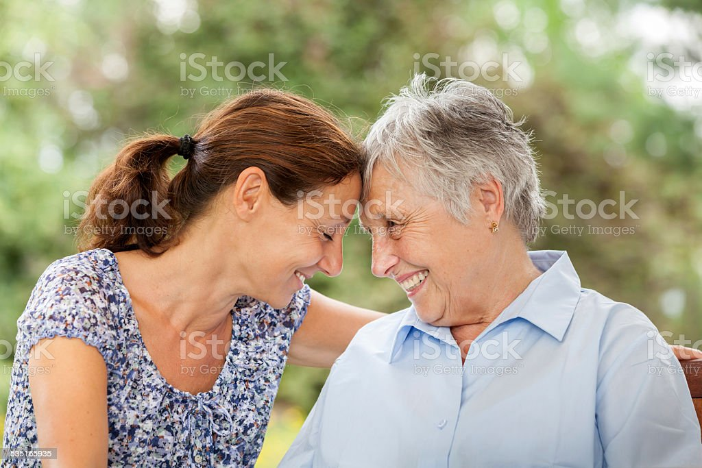 Senior woman and caregiver outdoors in a garden stock photo