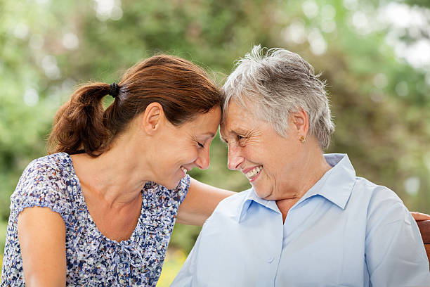 senior woman and caregiver outdoors in a garden - healthcare worker stock photos and pictures