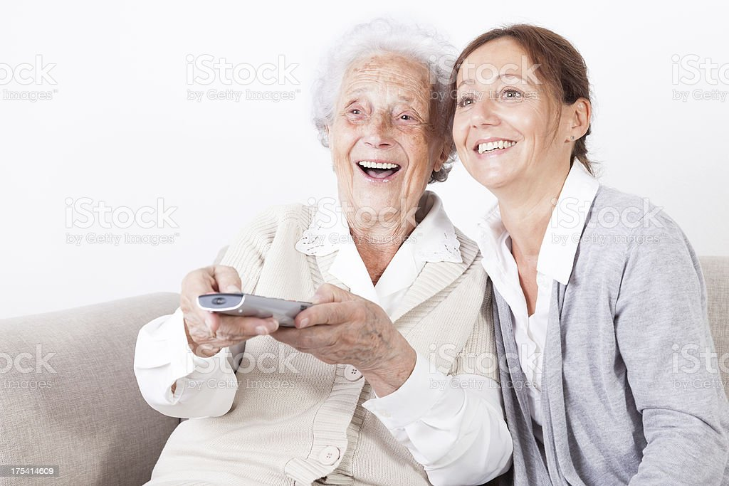 Senior woman and caregiver watching tv royalty-free stock photo