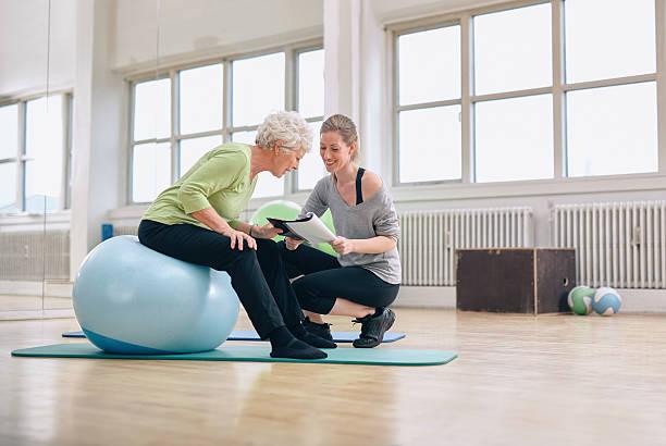 senior frau und trainer im blick fitness-bericht - trainingsplan frauen stock-fotos und bilder