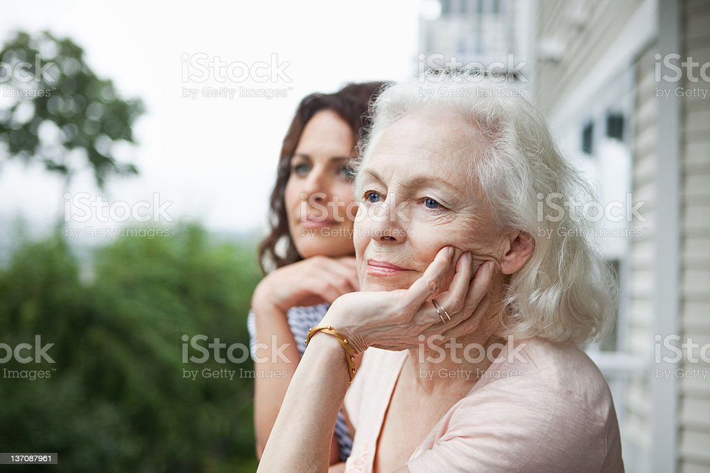 Senior woman and daughter relaxing on porch stock photo