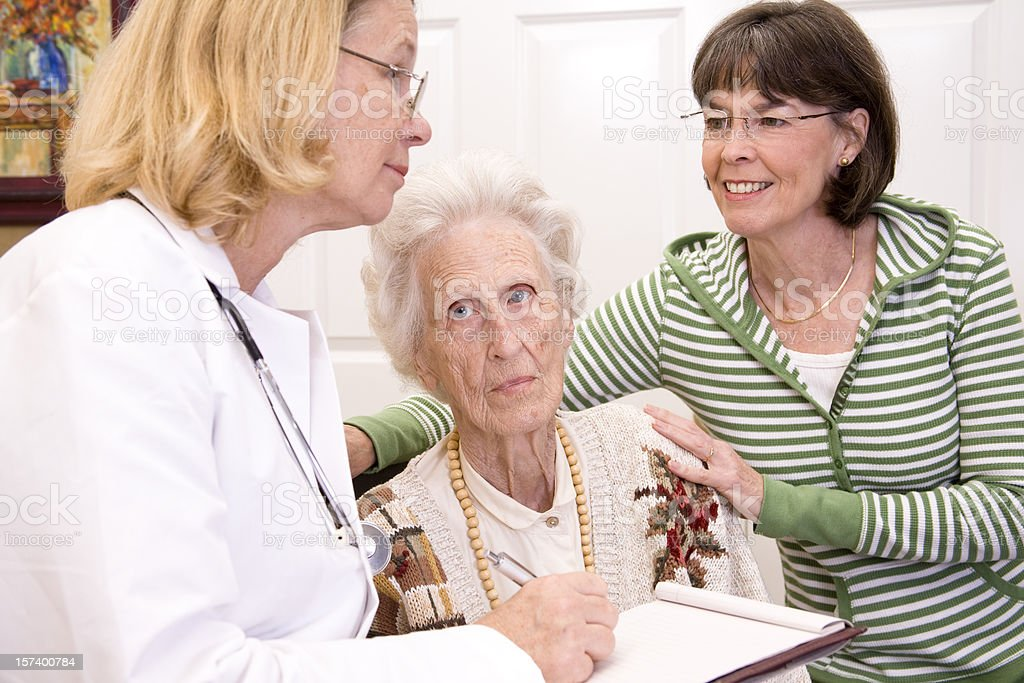 Senior woman and family consulting doctor royalty-free stock photo