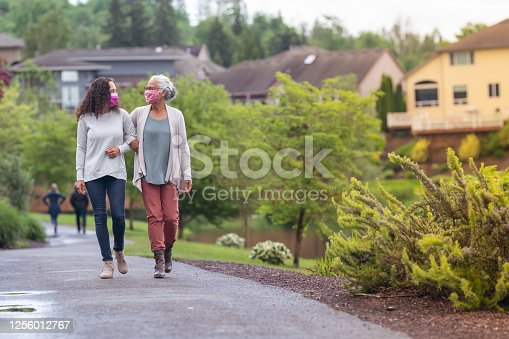 A mixed race senior adult woman is out for a walk with her adult daughter. The two women are wearing protective face masks and are walking with their arms linked. They are enjoying the outdoors and getting some exercise during COVID-19.