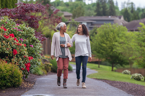 A senior woman links arms with her millennial Eurasian daughter as they happily walk through a natural parkland area and enjoy their time together.