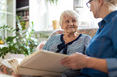 istock Senior woman and her adult daughter looking at photo album together on couch in living room 1248708507