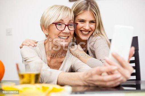 istock Senior woman and her daughter having fun and posing for a selfie 934109034